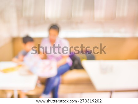 blur image of mother and her son enjoying lunch at restaurant  choosing meal from menu card.