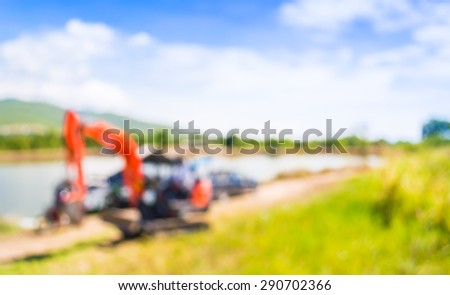 blur image of orange excavator doing lake construction and maintenance services under municipality authority on day time for background usage. - stock photo