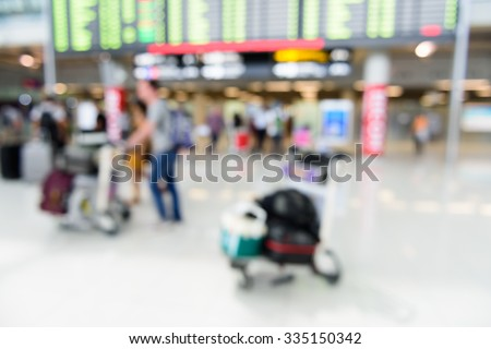 Blur image of passengers at flight arrival board in airport, Abstract background. - stock photo