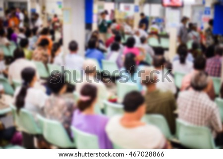 Blur  image  of  people in the waiting area of the hospital.