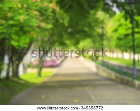 blur image of  the green garden for background and side walk  - stock photo