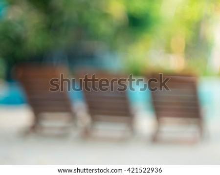 Blur image of wood chair and swimming pool bokeh in a beautiful beach resort - stock photo