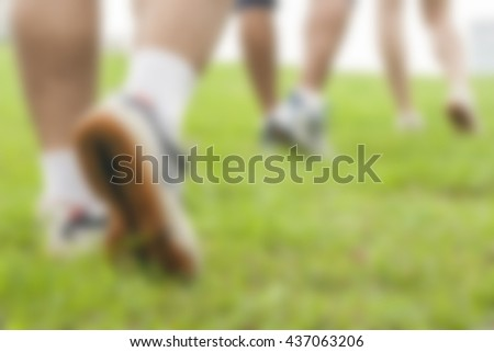 Blur image of Young people running in the park,for background usage. - stock photo