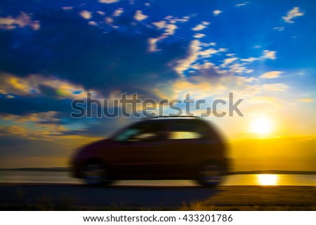 blur image. Silhouette of new car against blue and yellow sky with sunset light.  - stock photo