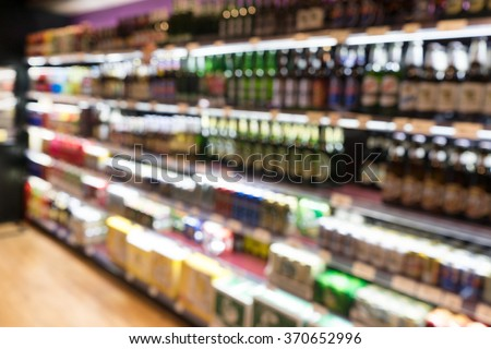 Blur of bottles of beer ( alcohol drink) on Shelf in Supermarket Background.for alcohol drink market concept - stock photo
