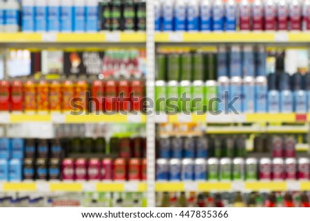 Blur of bottles of beer, cider and other alcohol drinks on Shelf in Supermarket Liquor Part - stock photo