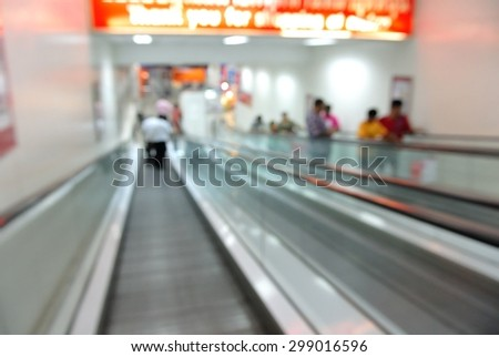 Blur of Defocus Background of People Going Down with Escalator - stock photo
