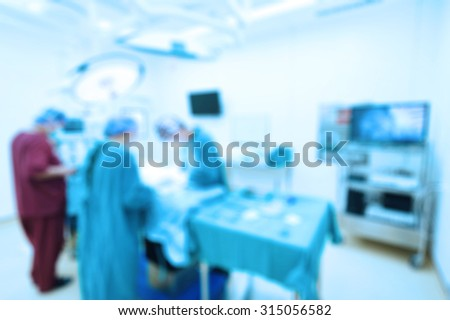 Blur of group of veterinarian surgery in operation room take with art lighting and blue filter - stock photo