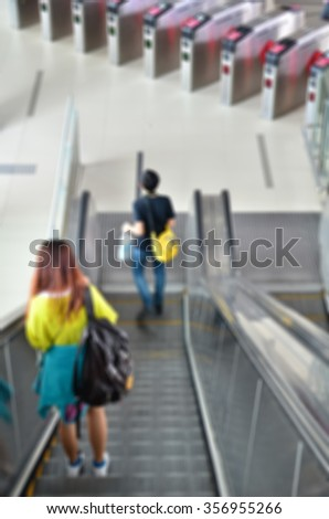 Blur of people going down at escalator - stock photo