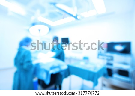 Blur of two veterinarian surgeons in operating room take with art lighting and blue filter - stock photo