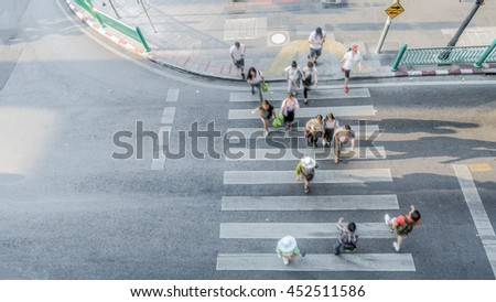 Blur people are moving across the pedestrian crosswalk in the city road (on top view) - stock photo