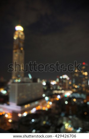 blur photo of high-rise tower against  night skyscape and the bokeh light of city in dark night time                                - stock photo