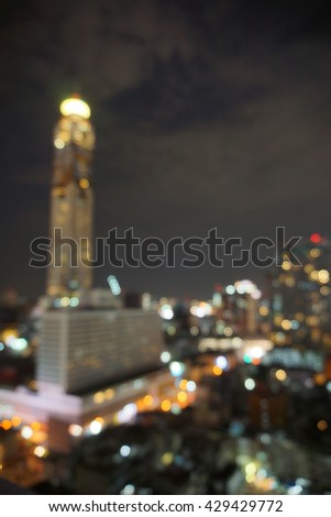 blur photo of high-rise tower against  night skyscape and the bokeh light of city in dark night time - Bangkok,Thailand                               - stock photo