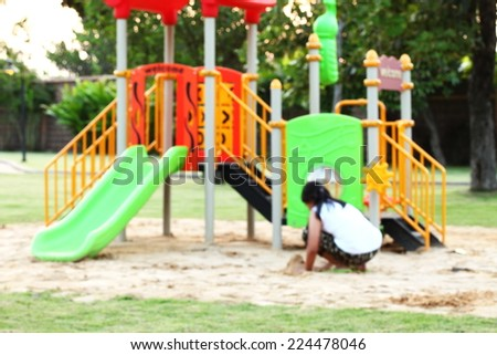 Blur playground scene in the photo represent one young girl play at the playground in blur focus also. - stock photo