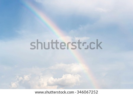 Blur rainbow on a background of blue sky and clouds - stock photo