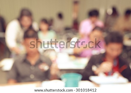 Blur shot on student in convention classroom with blurred activities - stock photo