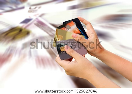 blur two hand holding credit cards on blur banknote background - stock photo
