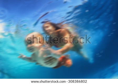 Blur underwater background. In blue pool young  mother swimming with baby son - dive underwater with cheerful boy. Healthy family lifestyle and children water sports activity and lessons with parents - stock photo