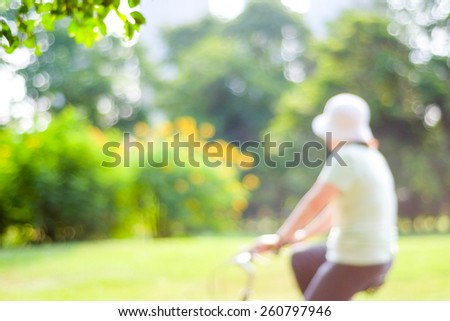 Blur woman riding bicycle in park with bokeh light background, spring and summer activity - stock photo