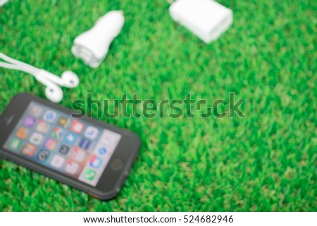 Blured picture : smartphone and accessories on grasses