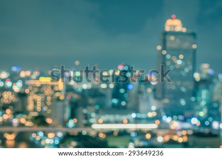 Blurred abstract background aerial view of Bangkok cbd downtown city night lights colorful bokeh in cool vintage cyan turquoise blue tone: Central business district on electric train line over river - stock photo
