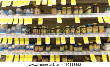 Blurred abstract background inside pharmacy store with arranged variation of pharmaceutical and medical supplies product in label on shelves display. Indoor drug store with blurred medicines. Panorama