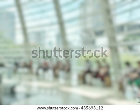 Blurred abstract background interior view looking out toward to office shopping mall lobby   glass curtain window wall frame with people: Blurry perspective of reception hall to building waiting hall - stock photo