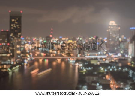 Blurred abstract background of aerial view of city night lights polygon bokeh in warm vintage color tone: Blurry retro style nightlife natural bokeh of Bangkok downtown central business district      - stock photo