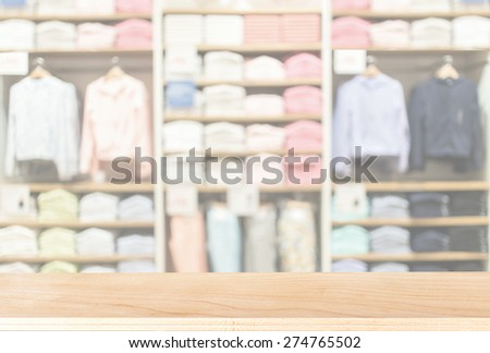 blurred abstract  background of empty wooden table in the multicolored cotton clothing on the shelves of fashion shop. background for product display template