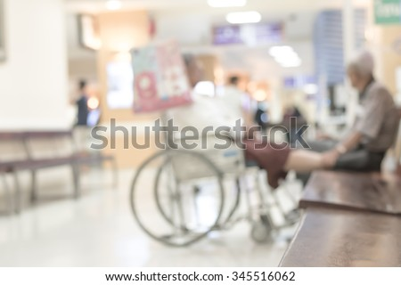 Blurred abstract background of hospital interior waiting hall/ corridor with patient on wheelchair in front of nurse station and OPD - out patient clinic department: Blurry view clinical indoor space - stock photo