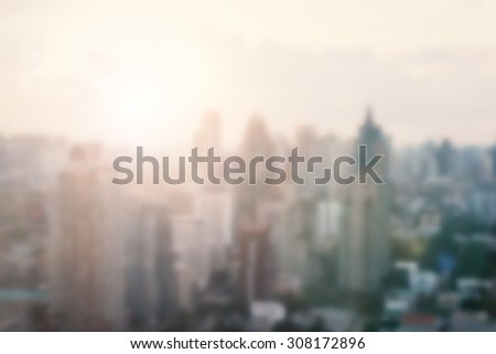 Blurred abstract background of morning gold light view over cityscape of downtown Bangkok with bright sun flare and bokeh in warm color tone: Blurry holiday travel backgrounds of urban smokey sunrise - stock photo