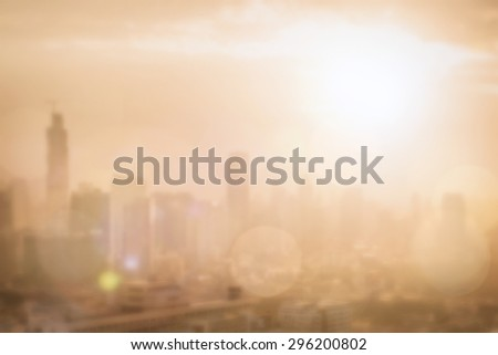 Blurred abstract background of morning sunrise gold light view over downtown Bangkok cityscape with bright sun flare and bokeh in warm color tone: Blur holiday travel backgrounds of smokey sun shine   - stock photo