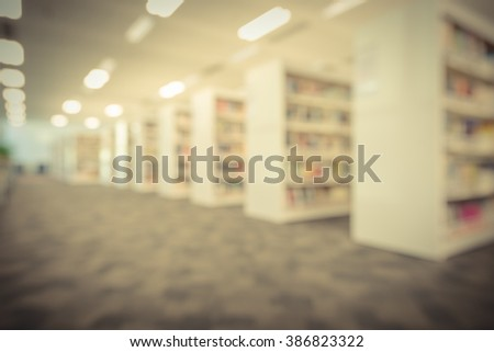 Blurred abstract background of public library interior with bookshelf aisle full of textbooks, literature and seating for students, faculties for reading. Self-study, educational concept/background. - stock photo