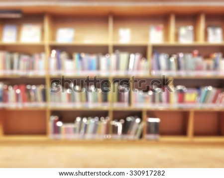 Blurred abstract background of public library interior with panel of bookshelves with collection of pocket books, magazines: Blurry perspective view of educational study room space with book shelves - stock photo