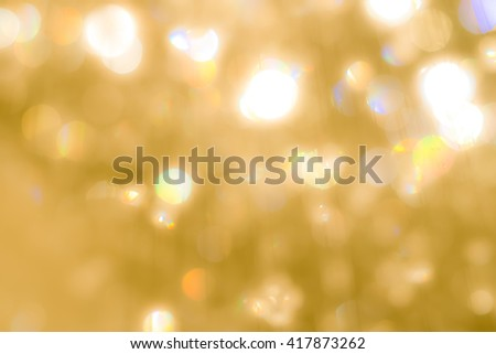Blurred abstract background of reflective yellow gold magical bokeh crystal mobile chandelier lamp shiny bright golden color lighting vintage colour tone: Sparkling lights of crystal glass reflection - stock photo