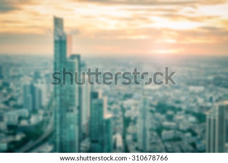 Blurred abstract background of rooftop view of downtown Bangkok urban skyline at sunset with bright sun flare in cool vintage color tone: Blurry twilight on city tour holiday travel vacation       - stock photo