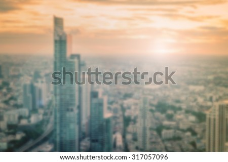 Blurred abstract background of twilight golden hour view over cityscape of downtown Bangkok with bright sun flare and bokeh in warm color tone: Blurry holiday travel backgrounds of urban smokey sunset - stock photo