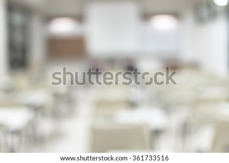 Blurred abstract background vacant empty seat row in school class lecture room w/ white projector slide screen in front: Blurry interior view back of the education classroom, no teacher nor student - stock photo