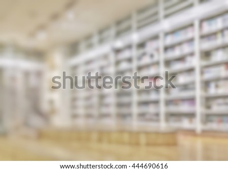 Blurred abstract background view of book shelves in public school library with people student behind aisle: Blurry interior perspective study room with table desks, chairs, seats & stacks of books   - stock photo
