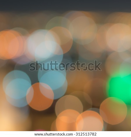 Blurred abstract background with city lights circle bokeh at night in warm vintage color tone: Colorful orange gold blue green urban nightlife illumination blurry bokeh of holiday travel vacation - stock photo