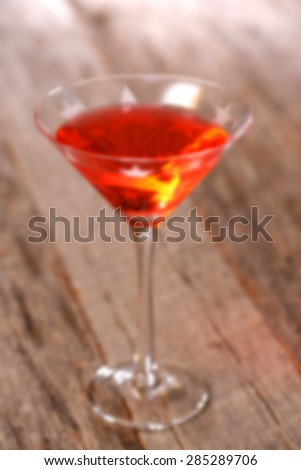 Blurred adult beverage cosmo colorful drink in martini glass on weathered, rustic tabletop - stock photo