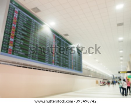Blurred airport electronic display screen flight timetable of departures and passengers are waiting around. Airport Departure Board. - stock photo