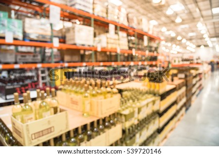 Blurred aisle of bottles in wine, champagne section of modern distribution warehouse. Defocused of storehouse interior aisle and rows. Inventory, logistic, export concept. Beverage alcohol background.