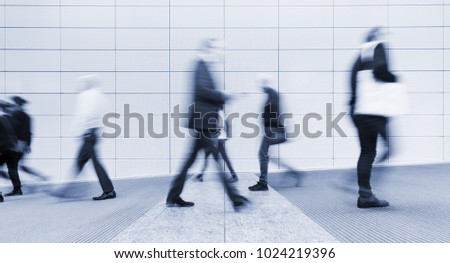 blurred anonymous people walking in a corridor