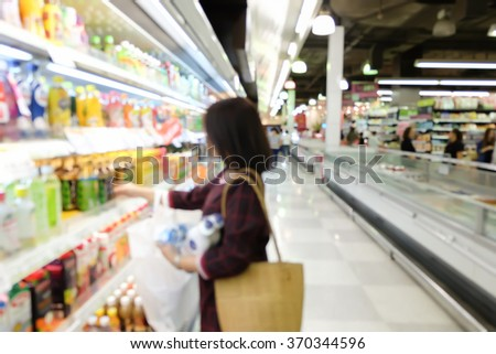 blurred asian woman choosing products/goods or beverage on shelves in supermarket store:blur people checking price in supermarket on weekend concept:blur girl shopping at market center conceptual. - stock photo