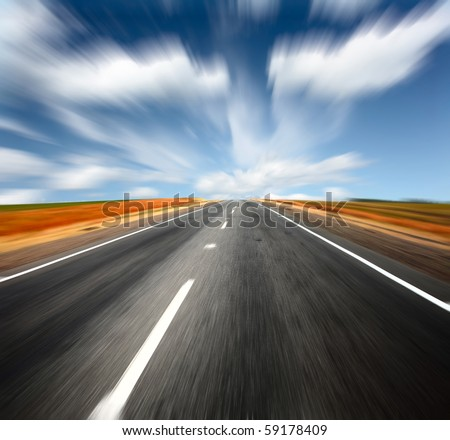Blurred asphalt road and blue sky with blurred clouds - stock photo