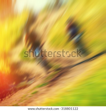 blurred background, a group of sporting cyclists riding on rough terrain - stock photo