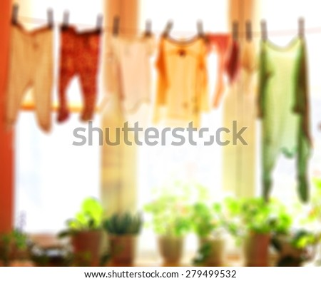 Blurred background : Baby laundry hanging on a clothesline with sun rising on a background. abstract  background - stock photo