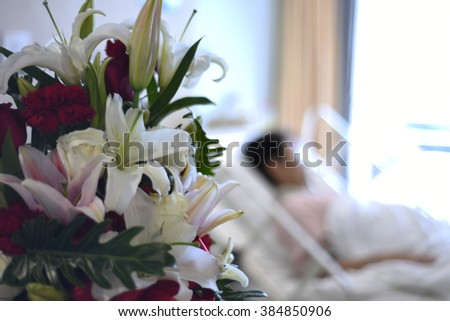 blurred background - bouquet flowers and patient in hospital room - stock photo