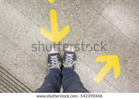 Blurred background Feet and two arrows painted on an road.
